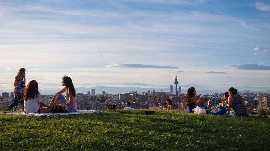 Grupos de gente haciendo picninc en el parque con vistas de Madrid al fondo