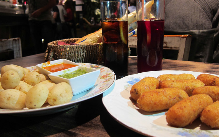 potatoes, croquettes and drinks on a bar